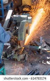 Worker Cutting of Steel in workshop