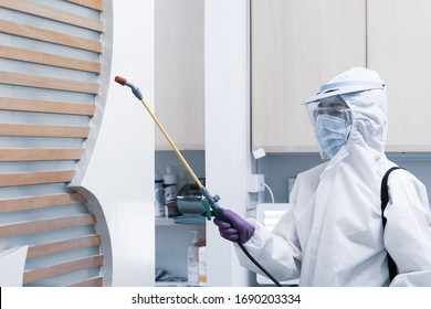 worker from decontamination services wearing personal protective equipment or ppe including white suit mask and face shield spraying disinfectant to cleaning coronavirus infection
