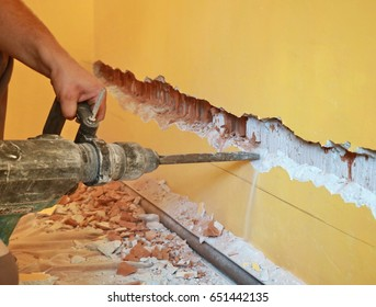 Worker demolish wall with electric chisel hammer
