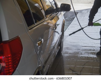The worker diligently washes the silver car