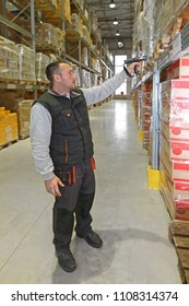 Worker in Distribution Warehouse With Handheld Barcode Reader