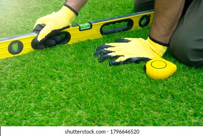 Worker doing the artificial grass installation and checking tilt with the level