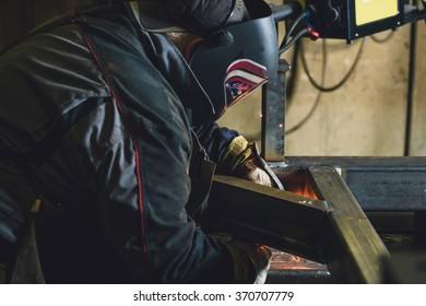 Worker dressed in protective uniform welding metal frame