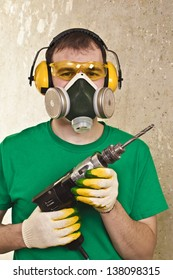 Worker with a drill in yellow protective glasses, ear plugs and respirator