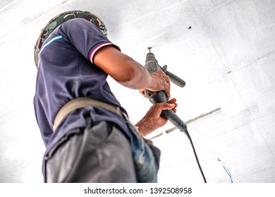 Worker is drilling holes on the ceiling  with electrical screwdriver drilling machine.
