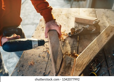 worker drills a hole in the bar with a screwdriver to connect making furniture