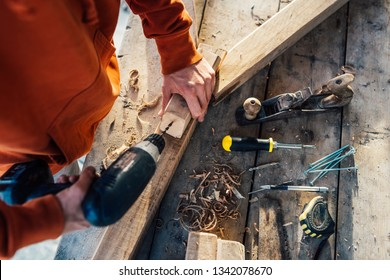a worker drills a hole in a wooden bar with a drill on wooden table in sawdust on sunset sunlight