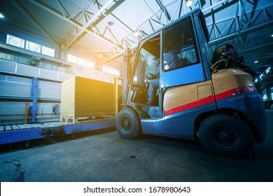 Worker driver of a forklift loader at warehouse of sandwich panels