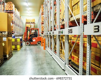Worker driver of a forklift loader at warehouse with boxes on pallet