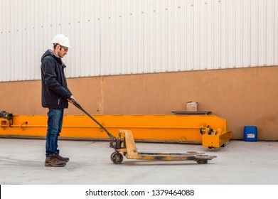 Worker driving empty hand pallet truck in a factory.