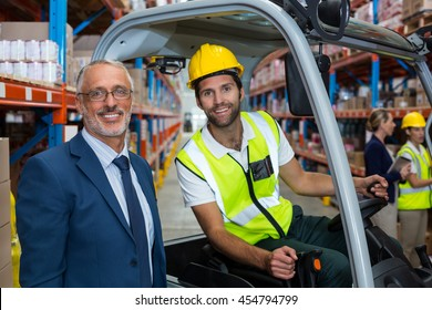 Worker driving forklift looking at camera with businessman in warehouse