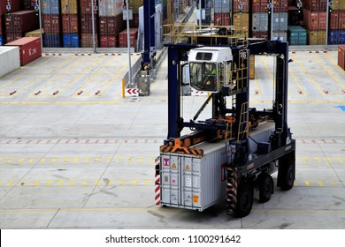 worker drove straddle carrier and moved a yang ming container on site of BEST terminal in Port of Barcelona, Spain, June 13, 2015