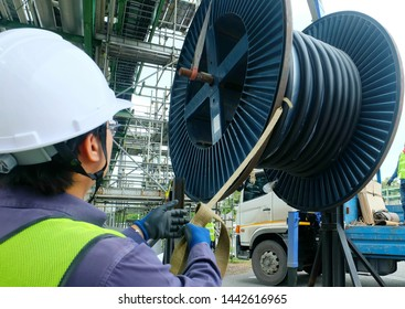 Worker during rope access rigger commencing high risk job to holding a safety tag line rope to control a load while crane, boom truck, truck loader is lifting big steel wire coil in chemical plant