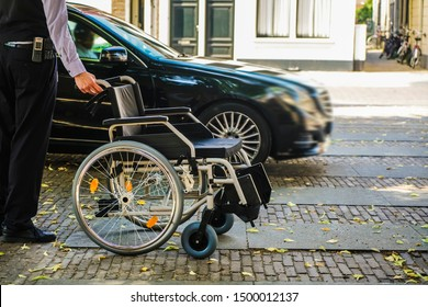 worker - employee greets a disabled person who came by taxi. hotel service. car parking near entrance. no face.