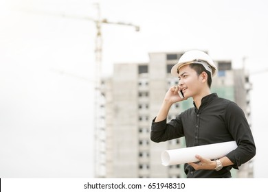 worker or engineer holding drawing in hands and uses mobile phone on background of new apartment buildings and construction cranes on background.Architect engineer concept.