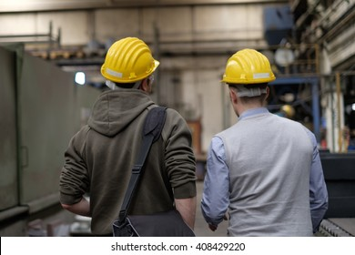 Worker and engineer working inside a factory