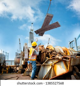 worker, engineering stevedore or foreman working under cargo loading lifting steel at risk of life, high level of insurrance working, unsafe working