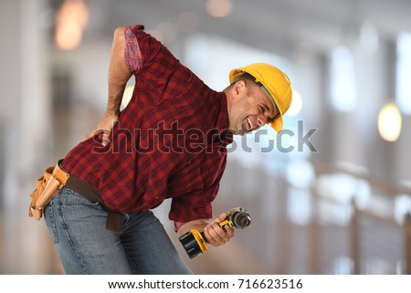 Worker experiencing sharp back pain while holding drill inside building
