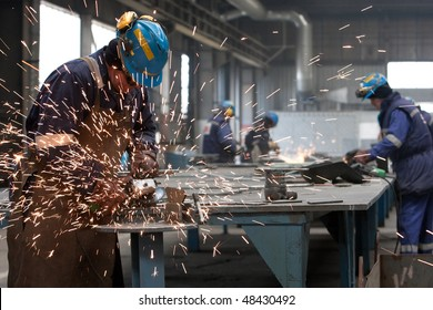 worker in factory grinding metal