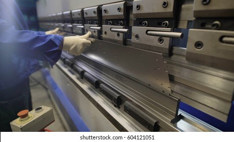 Worker in factory at metal skip machine putting work piece in. Man working with sheet metal and special machine tools for bending. Modern machines can accurately perform tasks.