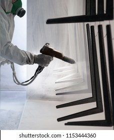 Worker at factory painting metal details with a gun of powder coating