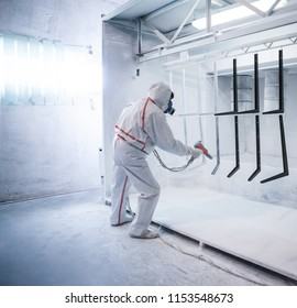 Worker at factory paints metal details with a gun of powder coating