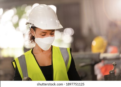 worker Factory people wearing face mask and safety suit. women working in factory. New normal life in factory with concern about covid-19 pandemic in human affect industrial business.