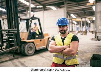 Worker in factory portrait with woman driving forklift in background