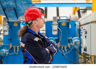 Worker in a factory wearing blue working suit and red helmet looking up in machines in the background