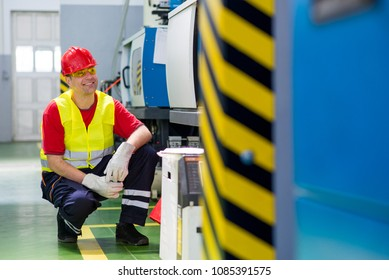 Worker in a factory. Worker wearing reflective west and red helmet crouching beside a machine