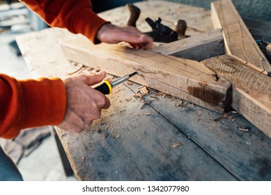 a worker fastens a wooden rail with a screw with a screwdriver, on a table in sawdust