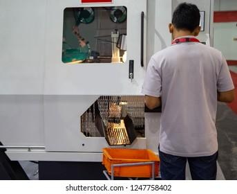 Worker feeding steel to NC High Speed Automatic Carbide Circular Saw