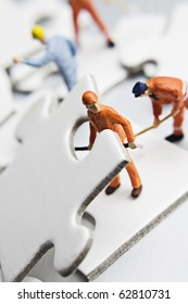 worker figurine with white jigsaw puzzle pieces