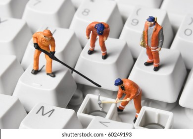 Worker figurines posed to look as though they are working on a computer keyboard.