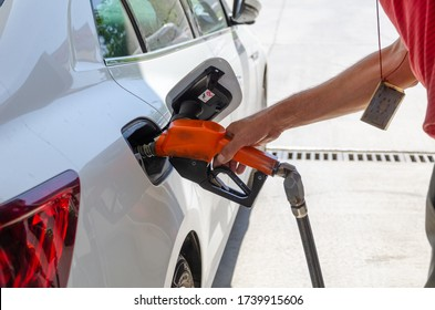 The worker filling up car fuel tank at gas station