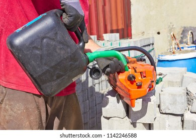 Worker filling fuel Into the chainsaw