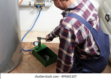 worker is filling up a heating system with a pump