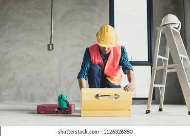 worker finding tools in construction box in working site