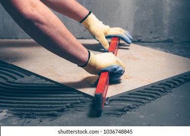 Worker finisher checks the quality of tile works on the floor with the help of a building level, highly skilled work
