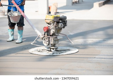 Worker finishing fresh concrete with power trowel