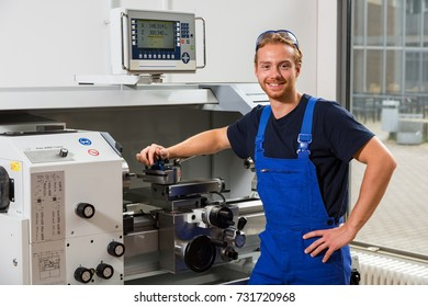 Worker or fitter posing in front of turning machine at a workshop