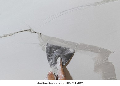 Worker fixing cracks on ceiling, spreading plaster using trowel