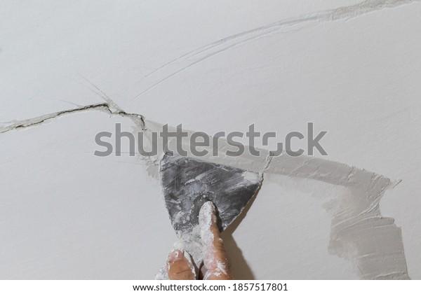 Worker fixing cracks on ceiling, spreading plaster using trowel