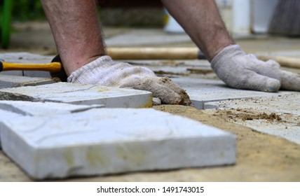 Worker in gloves lay square gray tiles