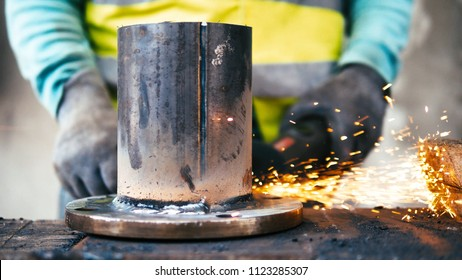 Worker with gloves and safety vest working on steel pipe with angle grinder, sparkles flying around, close up