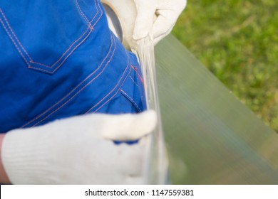 a worker in gloves seals the edge of the polycarbonate with a sticky tape.