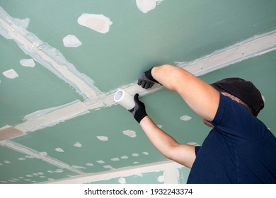 Worker glues mesh to drywall seams  - Shutterstock ID 1932243374