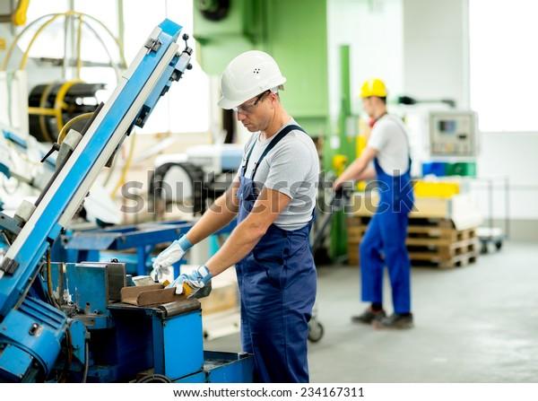 Arbeiter mit Schutzbrille und Helm auf der Maschine