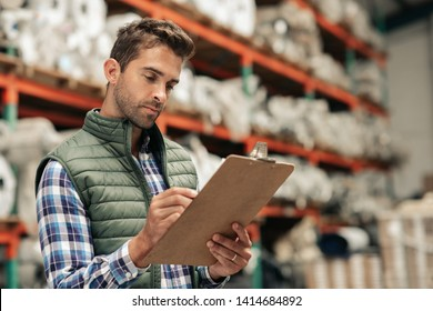 Worker going over inventory with a clipboard while standing on a carpet warehouse floor with stacks of stock on shelves in the background