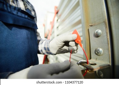 Worker in grey protective gloves putting red safety tag on lock hole